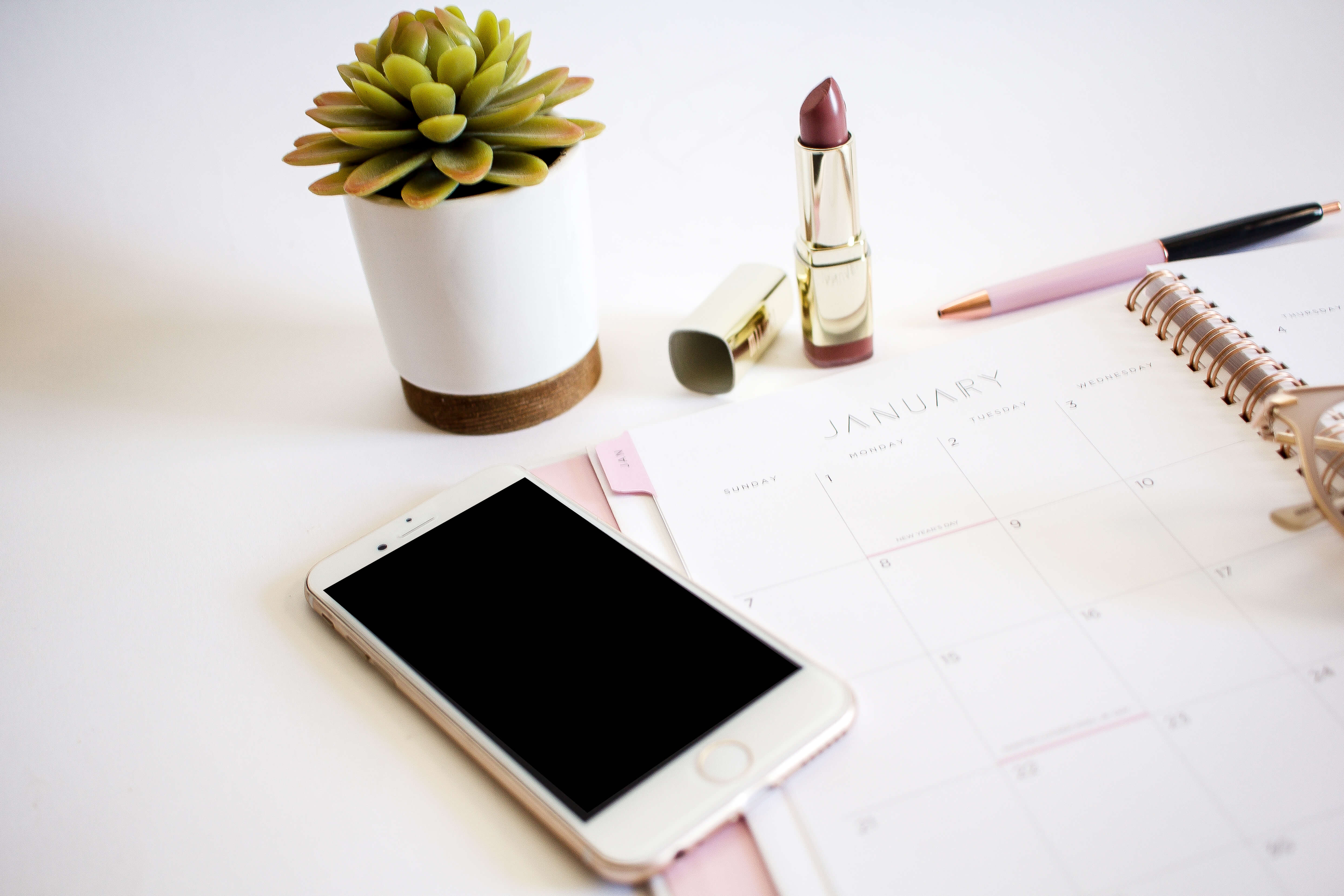 flat lay photo with cell phone, lipstick, calendar and plant