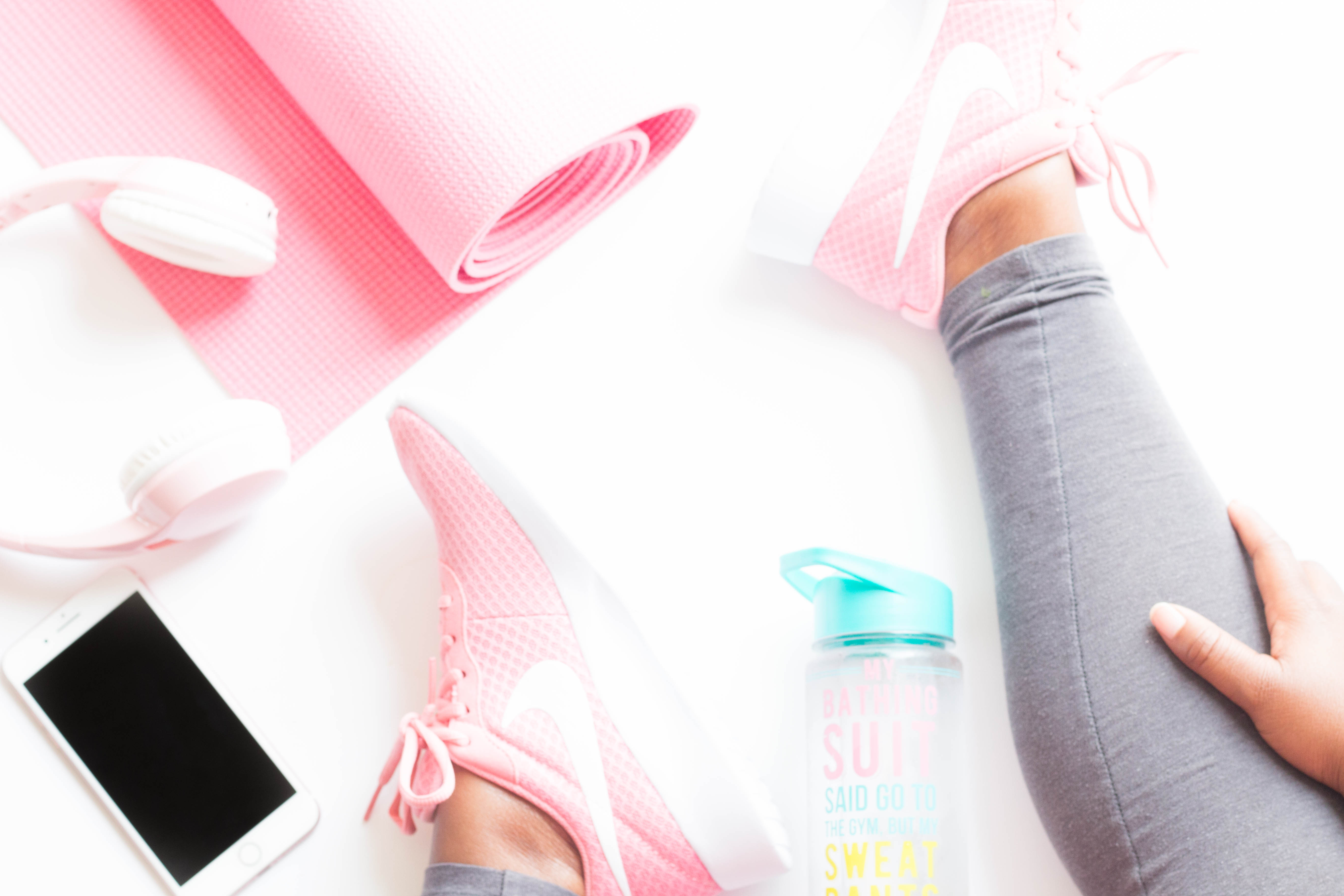 Flat lay with yoga mat, head phones, iphone, water bottle. Luara from Mom Connection helps help moms lose weight and talking about why moms have a hard time losing weight.