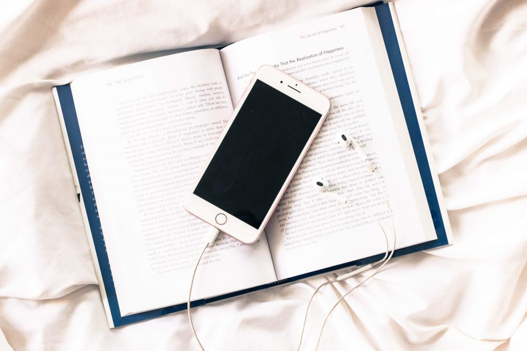 book with phone and ear buds